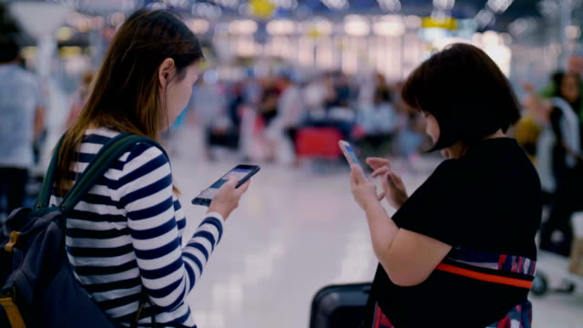 two womans using smart phone at the airport - exchanging stock videos & royalty-free footage