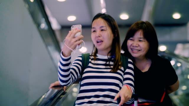 zwei womans mit smartphone am flughafen - flugpassagier stock-videos und b-roll-filmmaterial
