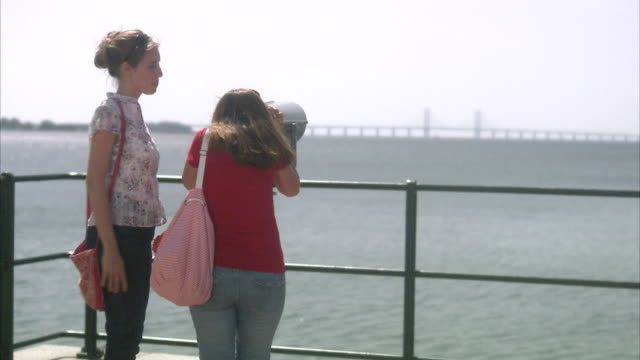 Two women admiring the Oresund bridge Skane Sweden.