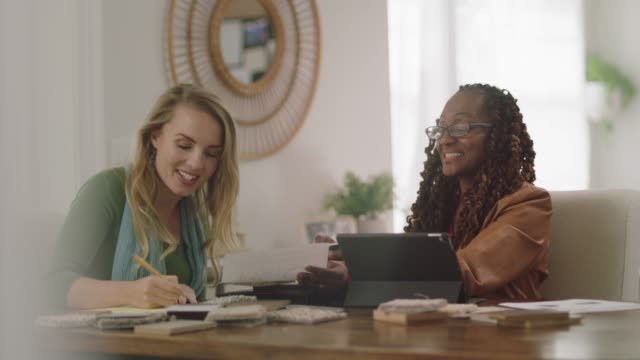 Two women agree while working together on an interior design project from home office.