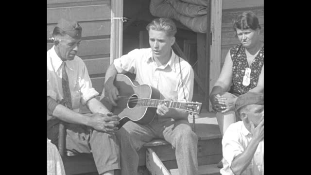 """two women and four men, one playing a guitar and singing // a man tacks a document to a wooded door under """"6th regimental hdq"""" sign, turns and walks... - hinweisschild stock-videos und b-roll-filmmaterial"""