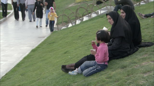 ms two women and girl eating ice cream on lawn in park, laughing, isfahan, iran - burka stock videos and b-roll footage