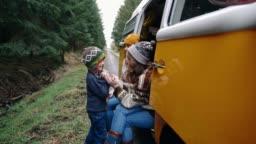Two women and little boy sitting in retro camper van