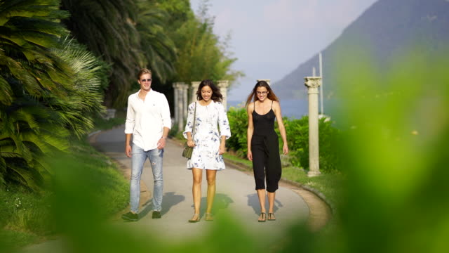 two women and one man walk along lakeside pathway talking and laughing - ticino canton stock videos and b-roll footage