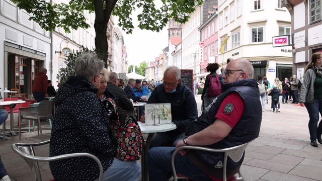 two women and two men, who said they did not mind being photographed, eat ice cream in an ice cream parlor in the shopping street in the city center... - four people stock videos & royalty-free footage