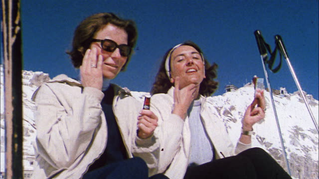 two women  apply sunscreen to their faces before skiing. - sonnencreme stock-videos und b-roll-filmmaterial