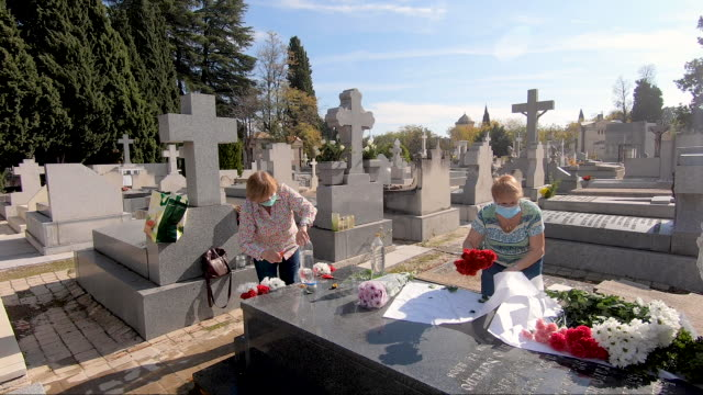 vídeos y material grabado en eventos de stock de two women arrange the flowers on the grave of their deceased loved one at the almudena cemetery on all saints day, the eve of the day of the dead... - espiritualidad
