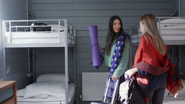 two women arriving in hostel dormitory with yoga mats - doorway stock videos & royalty-free footage