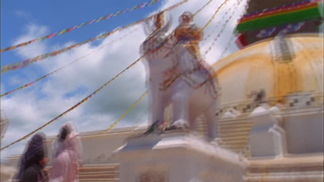 stockvideo's en b-roll-footage met two women ascend stone steps to temple decorated in multi coloured prayer flags available in hd. - gelovige