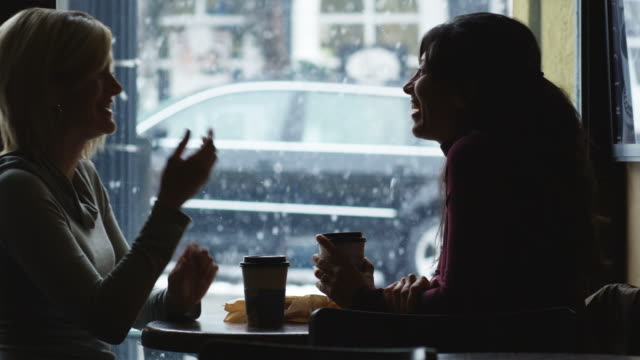 two women at a coffee shop talking - park city utah video stock e b–roll