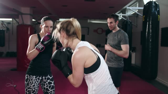 two women at box training with their coach watching over them - boxing women's stock videos & royalty-free footage