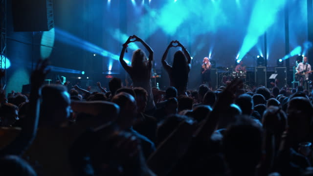 ds two women at concert making heart shape with hands - back lit stock videos & royalty-free footage