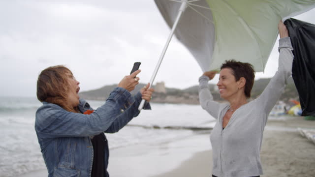 two women at rainy Ibiza beach with umbrella - having great fun and talking photos with smart phone