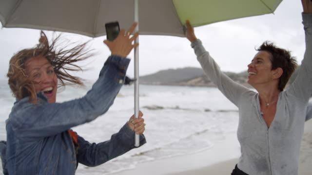 two women at rainy Ibiza beach with umbrella - having great fun under umbrella