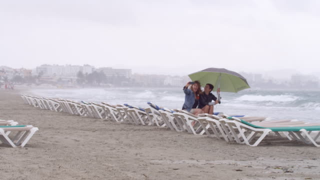 vídeos de stock e filmes b-roll de two women at rainy ibiza beach with umbrella - taking selfies - chapéu