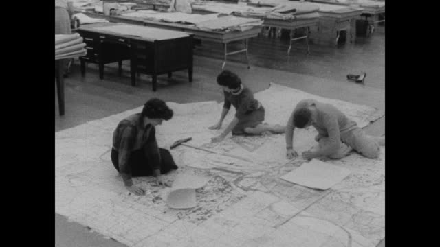 vídeos y material grabado en eventos de stock de 1960 two women at the census bureau take off their shoes and work with large maps on the floor - calzado