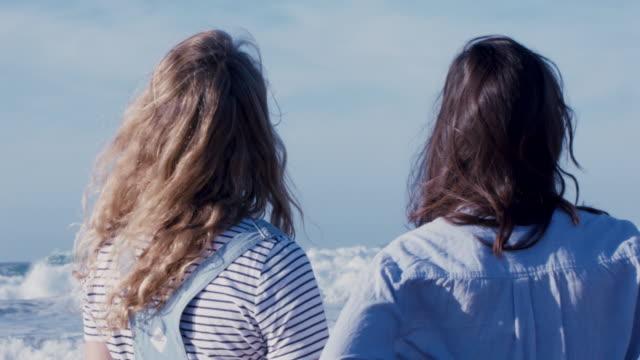 vídeos de stock e filmes b-roll de two women at water's edge on beach in portugal - water's edge