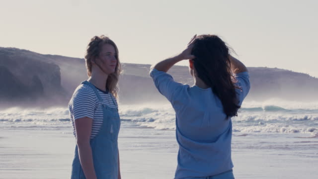 two women at water's edge on beach in portugal - sorglos stock-videos und b-roll-filmmaterial