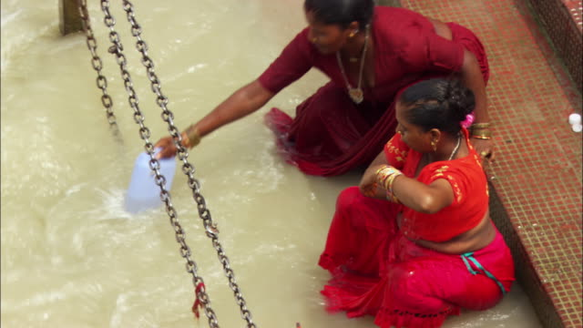 Two women bathe in the Ganges River in India. Available in HD.