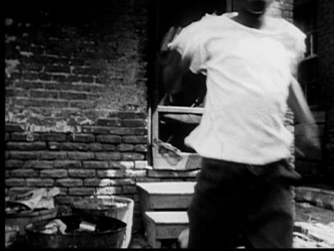 vidéos et rushes de 1953 ws two women being startles as they talk/ ms man leaning out window/ boy running out of house/ vs people running down sidewalk/ ha ws people crowding around something behind houses/ baltimore, maryland - maryland état
