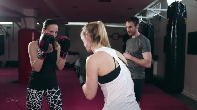 two women boxing in slow motion with each other while the coach stands besides them - boxing women's stock videos & royalty-free footage