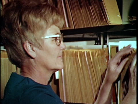 1970 montage two women browsing files at property tax assessors, los angeles, california, usa, audio - file clerk stock videos & royalty-free footage
