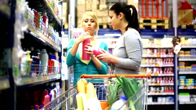 two women buying cosmetics in supermarket. - shampoo stock videos & royalty-free footage