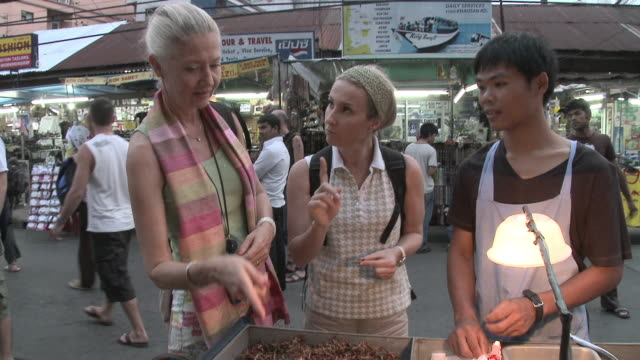 ms tu two women buying grasshoppers in busy city street, bangkok, thailand - thai culture stock videos & royalty-free footage