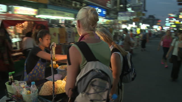 stockvideo's en b-roll-footage met ms ds two women buying pad thai food in city street at night, bangkok, thailand - thailand