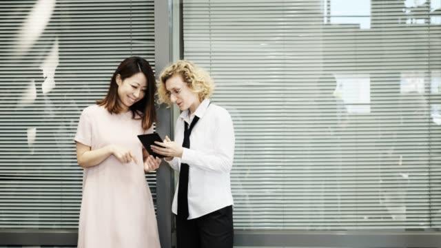 2 人の女性は、タブレット端末を見ながらチャットします。 - 若い女性点の映像素材/bロール