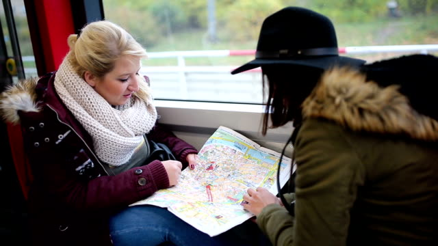 two women checking the city map - trolley bus stock videos & royalty-free footage