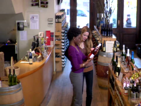ms, ha, two women choosing wine in liquor store, soho, new york city, new york, usa - hand an der hüfte stock-videos und b-roll-filmmaterial
