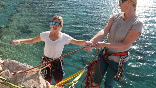 two women climb vertical rock above sea, sunrise - trovare video stock e b–roll