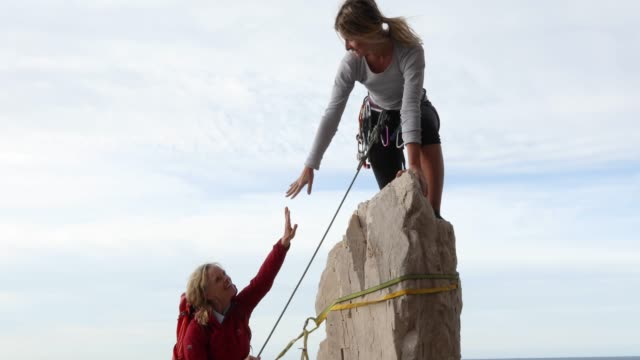 two women climb vertical rock above sea, sunrise - scoperta video stock e b–roll