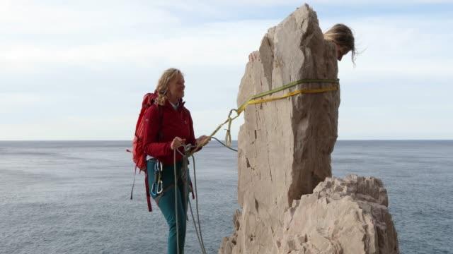 vídeos y material grabado en eventos de stock de dos mujeres suben rocas verticales sobre el mar, el amanecer - abrigo