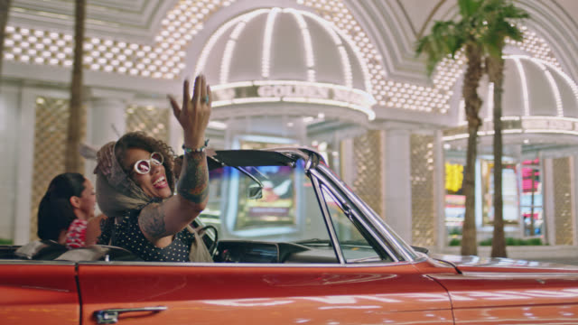 vídeos de stock, filmes e b-roll de two women cruising through downtown las vegas in classic convertible throw hands in the air and blow kiss at camera. - despedida de solteira