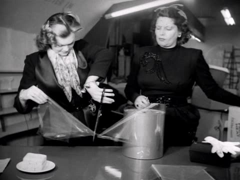 two women cut a section of plastic film to wrap up some sandwiches - wrapping stock videos and b-roll footage