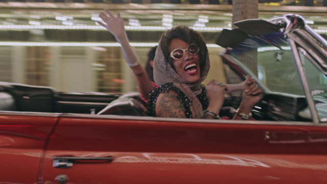 Two women dance and sing in shiny red convertible on night out in Las Vegas.