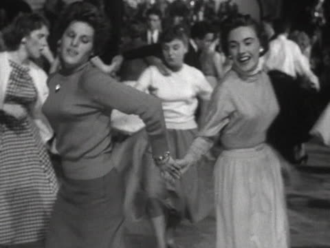vidéos et rushes de two women dance to rock and roll music in a dance hall. - rock