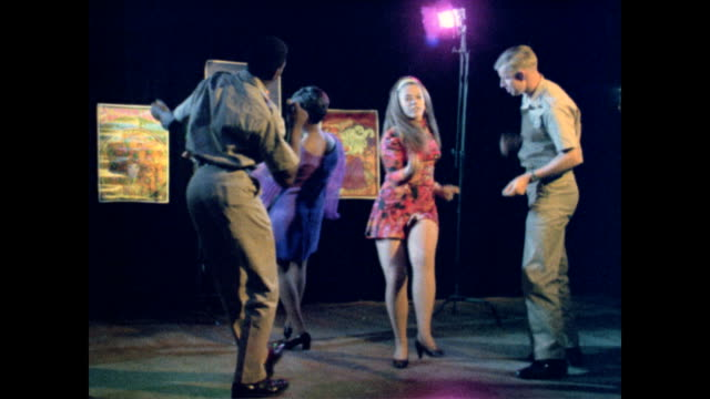 / two women dancing at club with two soldiers in uniform as voice over discusses how far women have come in recent years / CU disco lights and woman...