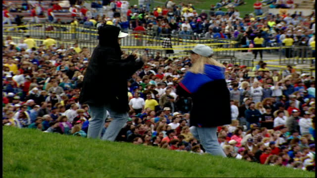 two women dancing on lawn at farm aid concert with audience in background in ames, iowa - お祭り好き点の映像素材/bロール