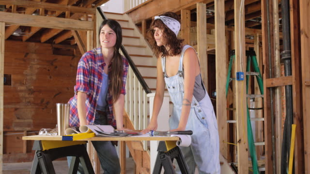 two women discuss renovation plans, and then high five. - renovation stock videos & royalty-free footage