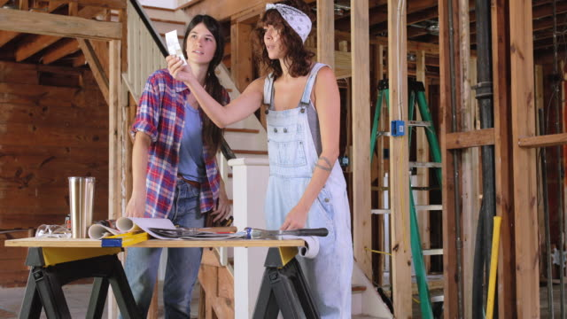 two women discuss renovation plans. - bib overalls stock videos and b-roll footage