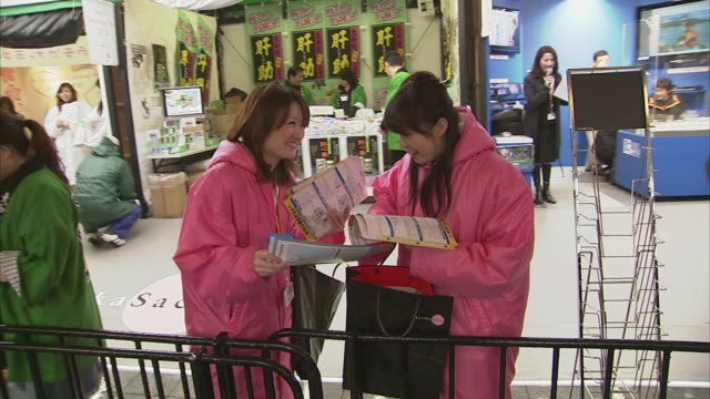 ms two women distributing fliers waving to camera, tokyo, japan - オーバーコート点の映像素材/bロール