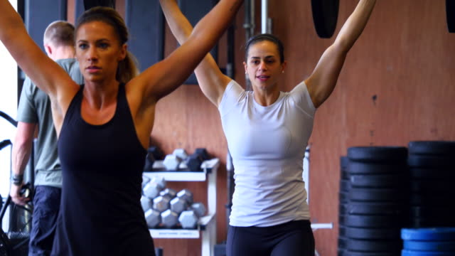 MS Two women doing barbell walking lunges while working out in gym gym