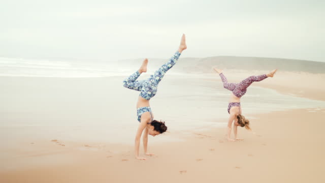 Two women doing handstands and high fives on the beach
