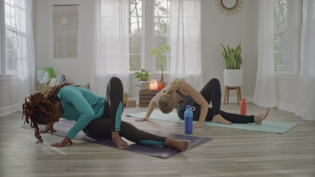 Two women doing home yoga workout shift positions from seated deep trunk twist to reverse plank.