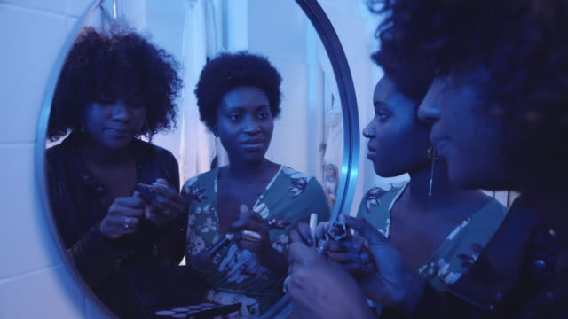 vidéos et rushes de two women doing make-up in the bathroom mirror - coiffure afro