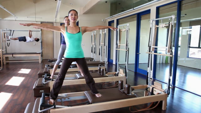 two women doing pilates, man in background - pacific islander background stock videos & royalty-free footage