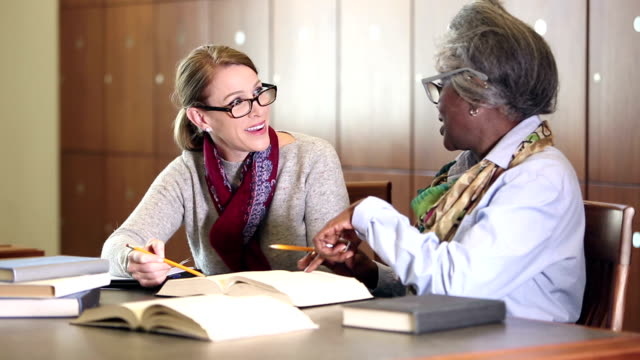 zwei frauen forschen gemeinsam in der bibliothek - lesebrille stock-videos und b-roll-filmmaterial